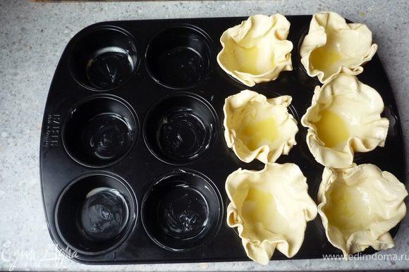 Выкладывать тесто в смазанную маслом форму для маффинов. Разогреть духовку до 200°C.