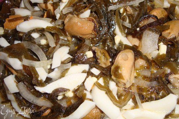 Мелко порезать лук, добавить морскую капусту (если жидкости в баночке слишком много - лучше слить), подкопченные мидии, мелко порубленные яйца, перец и заправить маслом от мидий.
