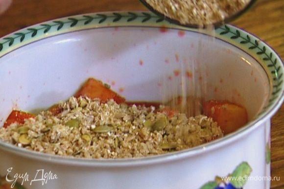 В глубокую форму для выпечки выложить фруктово-ягодную массу, присыпать крошкой с семечками.