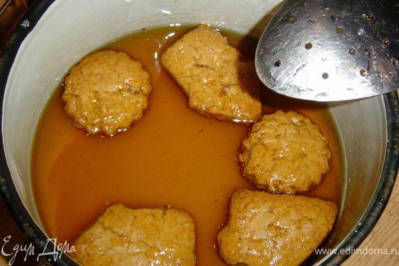 Пока запекается печенье, готовим сироп. Для этого в кипящей воде растворяем сахар и кипятим его 3-5 минут. Снимаем с огня, добавляем мед, хорошо перемешиваем и даем остыть. Горячее печенье опускаем на 1 минуту в сироп,