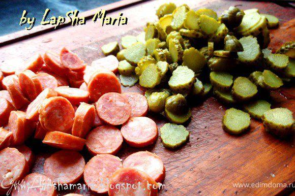 Нарезать колечками колбаски и корнишоны.