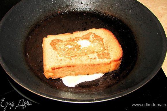 Переверните при помощи лопатки хлеб с яйцом. Я это делаю одновременно наклоняя сковороду и резко переворачиваю лопатку. Ничего, если белок немного расплескается.