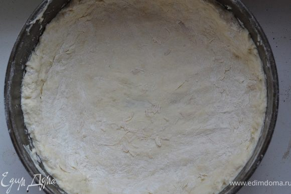 И для того чтобы разложить его в форму присыпаем на комок теста сверху немного муки и нажатием ладонями распределяем тесто.