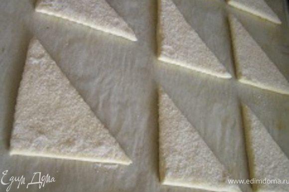 Каждый треугольник опустить с одной стороны в сахар, слекга придавить, выложить на противень (сахарной стороной вверх)