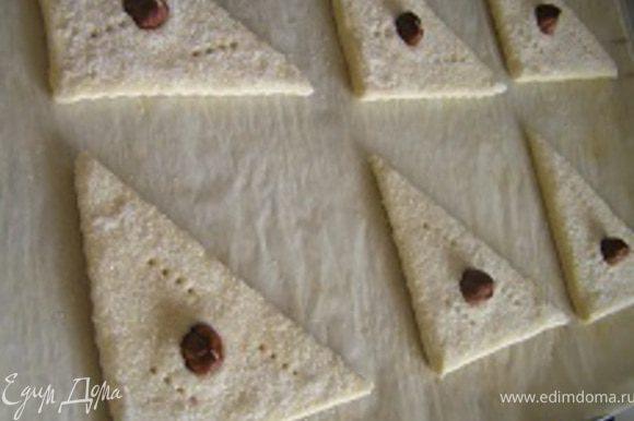 В центр каждого треугольника поместить орех, слегка вдавить.