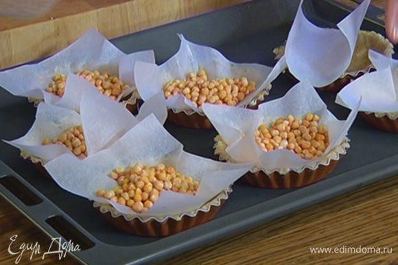 Вырезать из бумаги для выпечки квадраты чуть большего размера, чем формочки, положить их на тесто, сверху насыпать горох или фасоль.