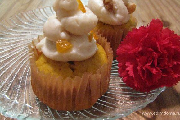Дать кексам немного остыть. Для крема смешать сир из сахарной пудрой, украсить цукатами и орехами.