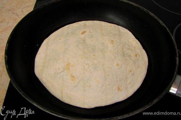 """Положите получившийся бутерброд на разогретую без масла антипригарную сковороду. Через минуту переверните бутерброд. Я обычно выкладываю тортильи на ладонь с растопыренными пальцами, переворачивая другой рукой сковороду, а затем перекидываю перевернутый """"бутерброд"""". Но! У меня большие руки, у вас так может не получиться. Зажаривайте еще минуту. На самом деле время зажарки вы должны найти сами."""