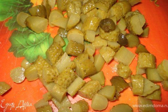 Корнишоны нарезать кубиками и добавить к овощам.