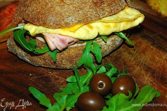 Арросто с омлетом (Arrosto e frittata). Это довольно простой панини, но он мне очень нравится. Я использую ржаную чиабатту, сразу оговорюсь, что я покупаю хлеб в итальянской пекарне недалеко от дома, но у кого есть дома «хлебопечка», могут испечь хлеб сами. Разрежем хлеб пополам, подогреем на гриле или тостере, потом выложим на нижнюю часть сыр, горсть рукколы, сверху тонкие ломтики мортаделлы, ветчины и чоризо.