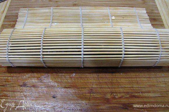Придерживая пальцами начинку начните заворачивать ролл вместе с бамбуковым ковриком. Как только вы сделаете один оборот, сразу высвобождайте бамбуковый коврик, чтобы он не завернулся внутрь ролла.