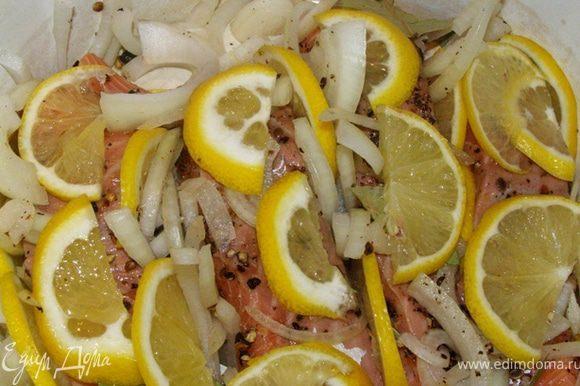 Тонко порежем 2/3 лимона кружками, затем перережем их пополам. Выложим на семгу пластинки лимона, всовывая их между кусками семги