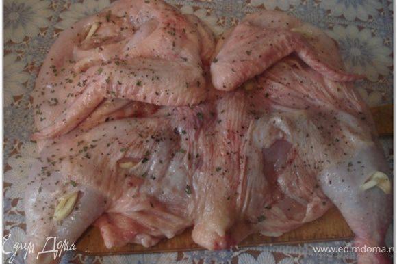 Цыпленка тщательно вымыть, обсушить и при необходимости обпалить. Положить цыпленка на разделочную доску и осторожно разрезать вдоль грудки. Чеснок очистить. 2 зубчика чеснока разрезать примерно на 10 тонких долек. Остальной чеснок мелко нарубить или пропустить через ручной пресс. Цыпленка хорошо отбить с обеих сторон, натереть солью, молотым красным и черным перцем. Сделать на коже небольшие надрезы и нашпиговать их дольками чеснока.