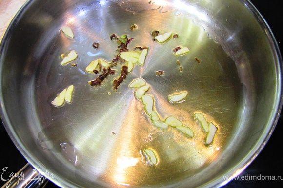 Разогрейте растительное масло в сковороде на среднем огне. Бросьте в сковороду чеснок и порубленные стебли.