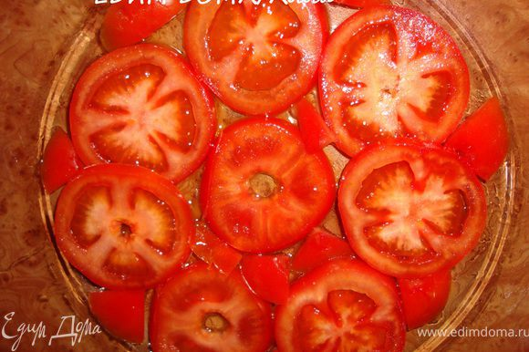 На дно формы, в которой будем запекать рыбу налить 1 ст.л. оливкового масла. Помидоры помыть и порезать кружочками. Выстелить дно смазанной формы кружочками помидоров.