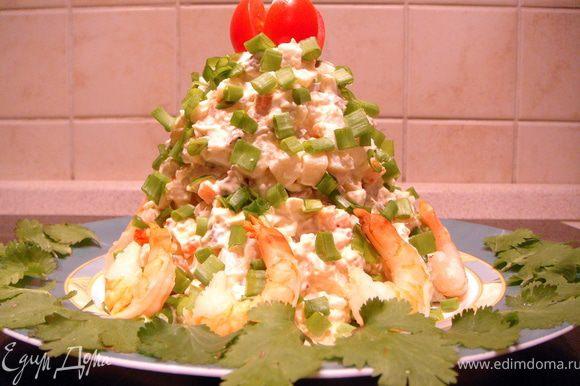 Выложить на тарелку в виде конуса, посыпать зеленым луком. Должно получиться похожим на елочку. Из помидорки черри сделать звезду. Выложить целые креветки как будто новогодние подарочки.