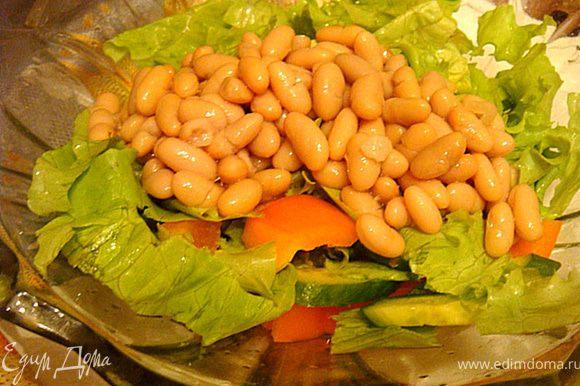 Выложить все в салатник, добавить фасоль (без жидкости). Чеснок достать,остудить, очистить и оставить дольками. Добавить в салат. Листья салата порвать.
