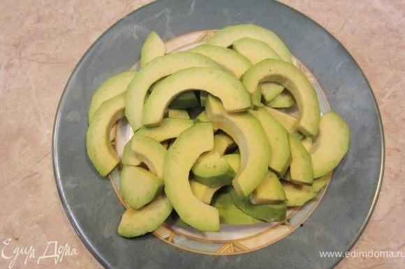 Разрежьте авокадо вокруг косточки, поверните половинки авокадо так, чтобы одна из половинок отделилась от косточки. Ударьте ножом по косточке, чтобы нож вонзился в нее. Поверните нож так, чтобы косточка отделилась от второй половинки авокадо. Если у вас спелый авокадо, то вы легко столовой ложкой вытащите половинки плодов из кожуры. Нарежьте половинки на полукольца.