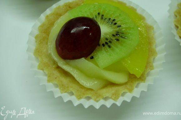 Тонкими ломтиками нарезаем киви и персик, виноград разрезаем пополам. Выкладываем фрукты поверх крема.