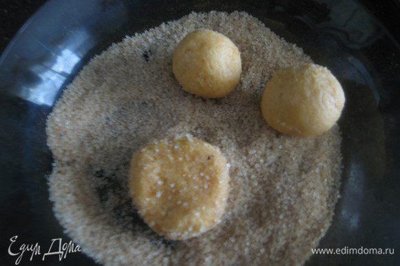 Чайной ложкой берем тесто, скатываем в руках быстро шарики, обмакиваем в сахар со специями и слегка приминаем.