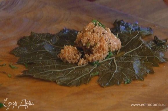 Выложить начинку из кускуса на виноградные листья и свернуть конвертиками.