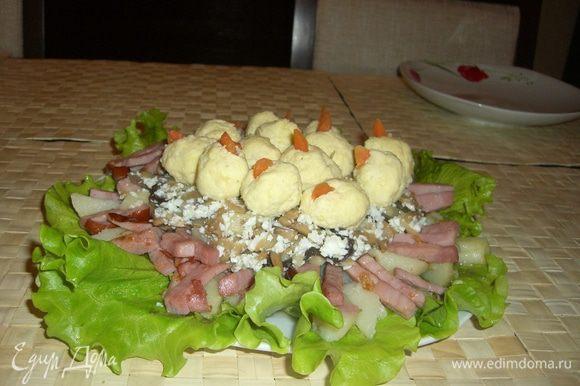 Картофель и капченное мясо выкладываем на листья салата в виде гнезда, добавляем туда лук с грибами и нарезанным белком. Вареную морковку охлаждаем и очищаем от кожуры. Скатываем небольшие шарики из сырно-чесночно-желтково-майонезной массы, в середину каждого из которых вкладываем половинку грецкого ореха. Теперь укладываем их в гнездо.