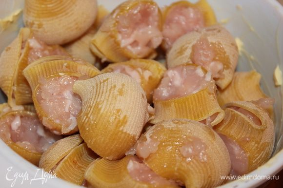 Складываем фаршированные лумакони в смазанную сливочным маслом посудину (у меня керамическая форма). Посыпаем нарезанным луком.