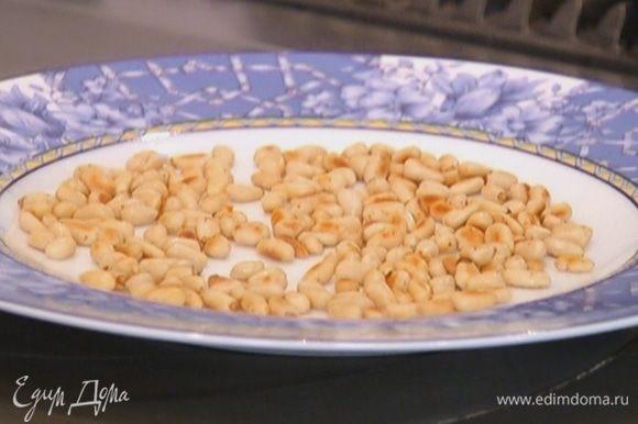 Разогреть сковороду и подсушить кедровые орехи.