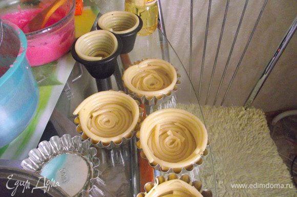 Выложить спиралью в форму для маффинов. По 6 макаронин на тарталетку примерно. На дне зазор тоже прикрыть кусочком спагетти.