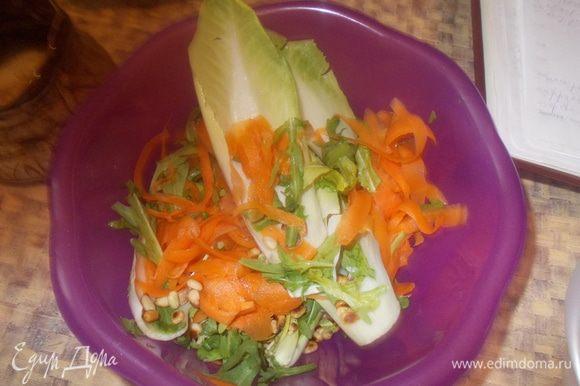 Морковь очистить, с помощью овощечистки нарезать тонкими длинными полосками. Опустить в кастрюлю с кипящей водой. Варить на медленном огне 2 мин., затем отбросить на дуршлаг и дать остыть.Руколу и цикорий вымыть. Цикорий разобрать на листья. В большой миске соединить морковь, руколу и цикорий. Посыпать кедровыми орешками.