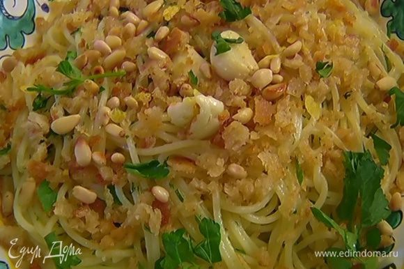 Спагетти выложить в блюдо, посыпать чесночно-хлебной крошкой, кедровыми орехами, лимонной цедрой и оставшейся петрушкой.