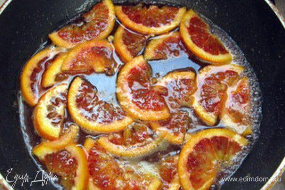 Нарезать цитрусовые кольцами. В сотейнике растворить, нагрев, сахар с 150 мл воды. Как только сахар растает, опустить цитрусовые. Поварить их в сиропе около 15 минут.