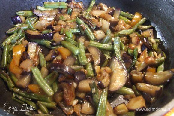 Обжарить баклажаны, фасоль и перец на подсолнечном масле на сковороде. Добавить 2 ст.л. соуса и мелко порубленный чеснок. Перемешать, выключить огонь и накрыть крышкой.