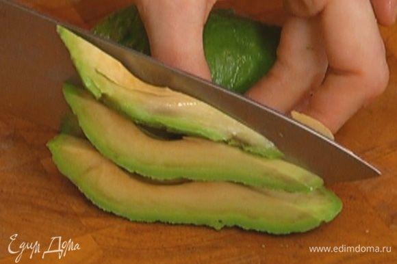 Авокадо очистить от кожуры, удалить косточку и нарезать тонкими дольками.