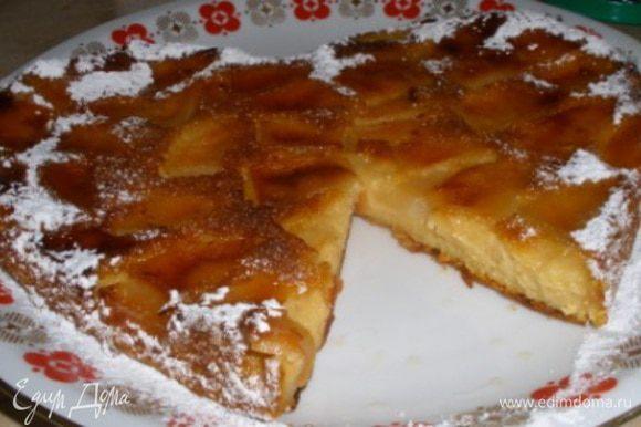 Перевернуть готовый пирог, выложить на тарелку вверх яблоками и украсить сахарной пудрой.