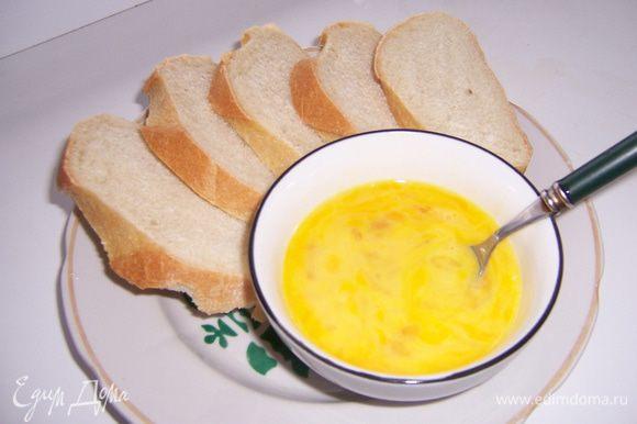 Выполнить нарезку хлеба на ломтики. Два яйца взбить в небольшой посудине.