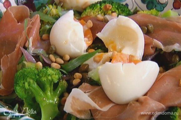 Яйца разломить пополам, выложить на салат, сверху посыпать каперсами и орехами.