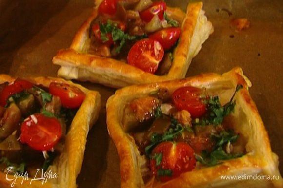 На сыр выложить измельченные помидоры с чесноком и базиликом и помидоры черри. Сбрызнуть пирожки оливковым маслом и запекать еще 2–3 минуты.