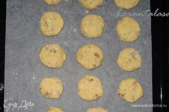 Добавить к этой смеси муку и пекарский порошок и хорошо перемешать, после чего добавить в тесто грецкие орехи и и шоколад. Из теста сделать шарики, которые затем расплющить в лепешечки-печенья и выложить их на противень с пергаментом.