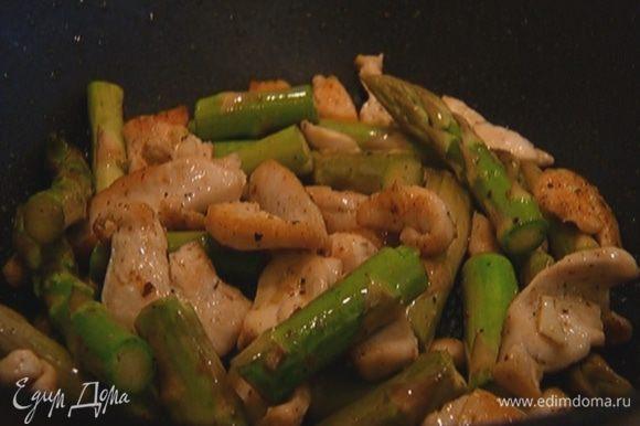 Добавить спаржу и чеснок, посолить, поперчить и готовить еще 2–3 минуты.