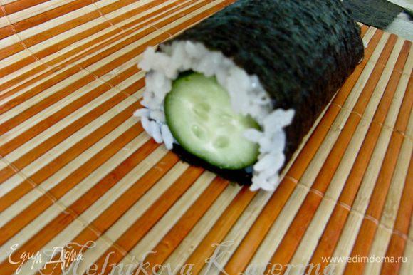 Обернуть нори с рисом вокруг огурца, чтобы получился один оборот.
