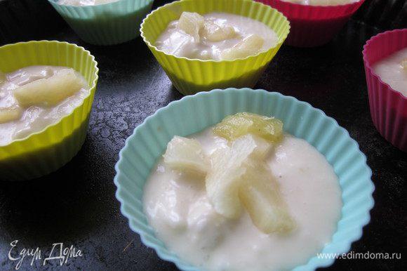 В миску влить 200 мл кокосового молока, 200 г сиропа, кусочки ананасов (оставить часть для верха), мед, растительное масло (предлагалось оливковое, но у меня подсолнечное без запаха) и уксус. Хорошо все размешиваем. Теперь добавляем муку смешанную с содой. Аккуратно перемешиваем, смесь на ваших глазах увеличится в объеме. Раскладываем по формочкам. Я сделала шесть маленьких кексов и один большой кекс в круглой форме. Сверху на тесто выкладываем кусочки ананасов, которые мы отложили.