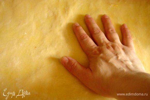 Сливочное масло растопить и обильно смазать им рабочую поверхность.Тесто переложить из миски на смазанный маслом стол.Руками растянуть тесто(оно получается очень мягким и поддатливым и растягивается легко) в большой прямоугольник,постоянно подливая масло на тесто.