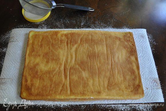 Перевернуть бисквит на полотенце и аккуратно снять пергамент.