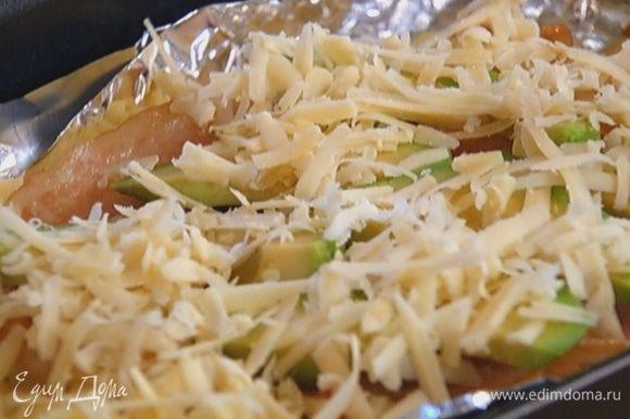 Вынуть картофель из духовки, разложить сверху авокадо, присыпать сыром и отправить обратно в духовку или под гриль на 3–5 минут.