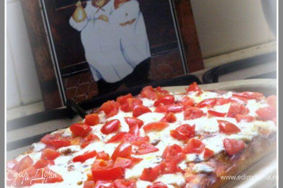 Разогреть духовку до 220°С. Пока духовка греется, нарезать моцареллу на маленькие кусочки толщиной 2-3 мм или кубики. Выпекать пиццу 10-12 минут, затем открыть духовку, сбрызнуть пиццу водой из распылителя и быстро выложить на неё моцареллу и другие ингредиенты по желанию и запекать ещё 10 минут.