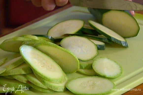 Кабачок и цукини вымыть и тонко нарезать наискосок под небольшим углом.