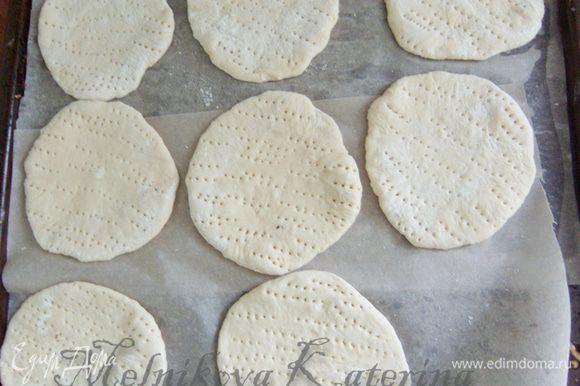 """Раскатать каждую часть толщиной примерно в 0,5 см. Противень выстелить пекарской бумогой, смазать сливочным маслом. Выложить """"лепешки"""", наколоть вилкой. Поставить в теплое и укромное место на 30-40 минут для подхода."""