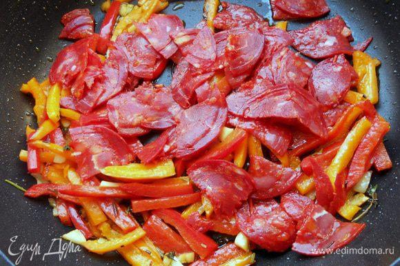 Присоединить колбасу и обжаривать еще с минуту.