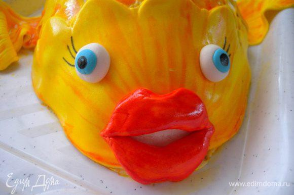 """Приклеить (под губки подложить немного белой мастики - зубки) ...Глазки (из белой и голубой мастики), реснички (пищевым фломастером) :-))). В остатки желтой краски капнуть красной и пройтись по основанию чешуек, плавников, хвоста и по """"мордочке"""""""